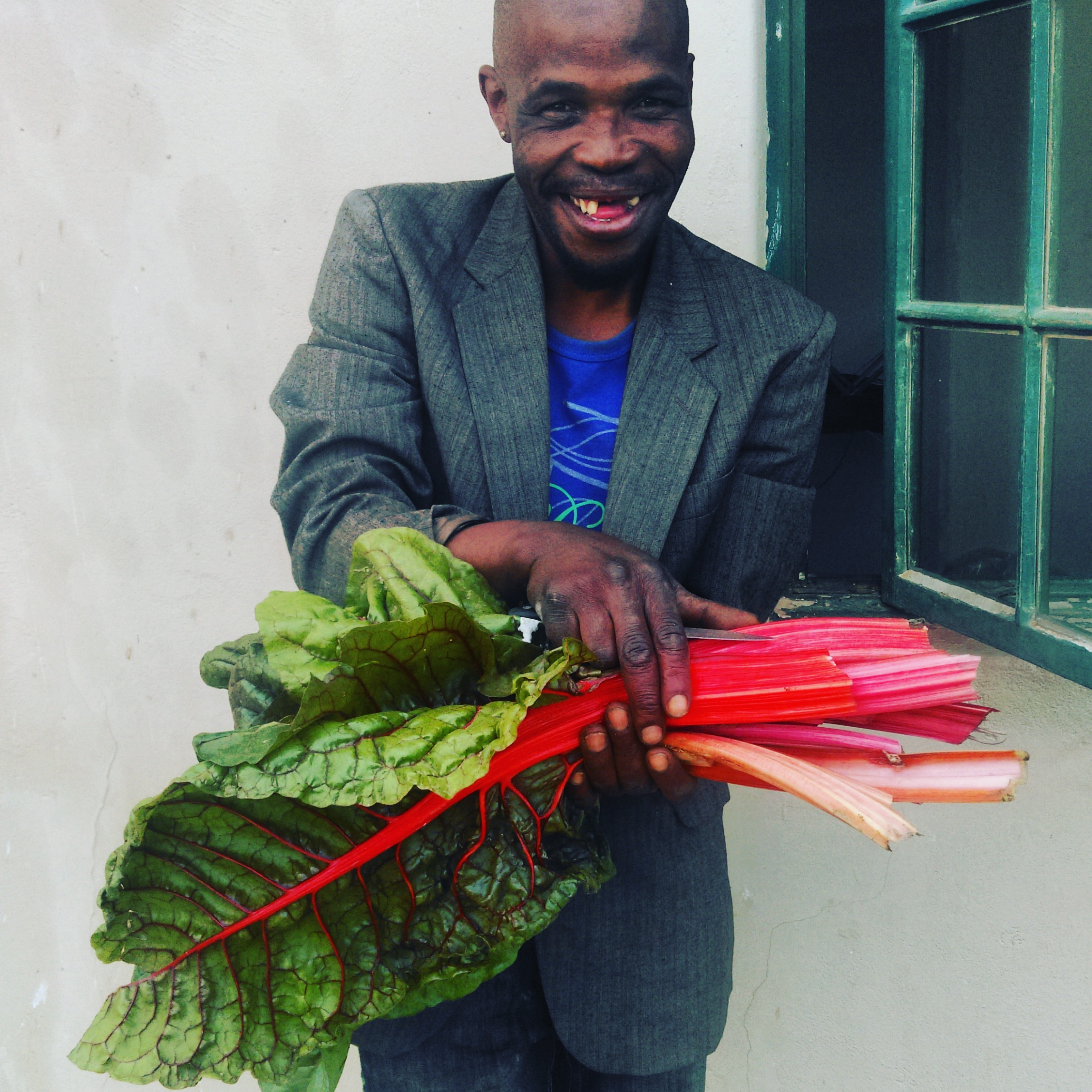 Russell, delighted with his first harvest from the garden.